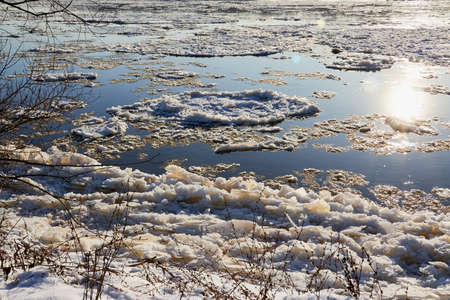 Ice drift on a river with blue high water and big water, white snow broken ice full of hummocks in it and sun reflection in sunny spring day Standard-Bild