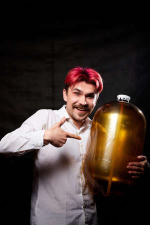 Young handsome guy with red hair in white shirt having fun with beer. Funny man with emotions on face with large bottle of beer and black background. Brewer and barrel. Happy alcoholic with alcohol