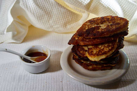 Pancakes on white plate and sweet liquid honey or caramel with a small spoon and with background. Delicious fried flour food. Unhealthy and harmful, but very tasty food Standard-Bild