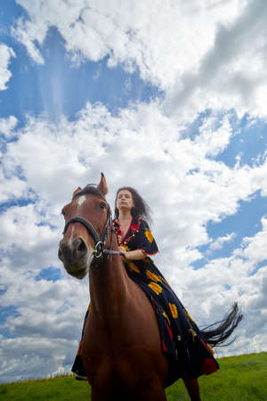 Beautiful gypsy girl on a horse in summer day and blue sky and white clouds background. Model in interesting dress posing during photoshoot