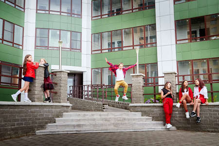 Group of fun children in stylish clothes near big modern house in the city in a summer, spring, or autumn day