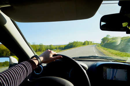 Car salon, steering wheel, hand of woman on it, mirror and view on landscape with road and nature at sunny summer or autumn day. Female traveler and driver in single trip during the coronavirus covid