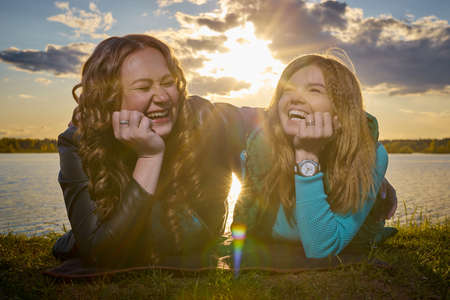 Two girls friends, sisters, cousins socializing and having fun on the shore or beach of a lake or river with calm water and sunset in the background on the horizon Standard-Bild