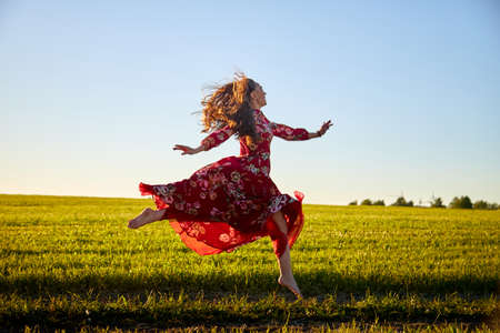 Beautiful woman or girl with magnificent figure and plastic movements walking and dancing in green field with trimmed grass in the setting sun during sunset with warm yellow light