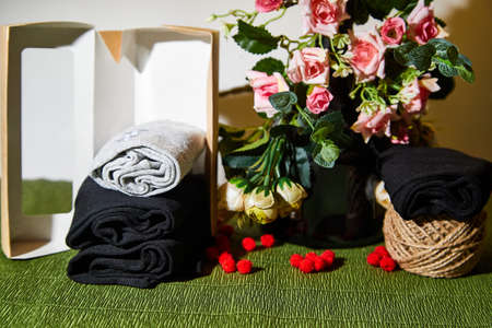 Several pairs of new male cotton socks with a brown cardboard box on a green surface and flowers background. The concept of coziness and comfort. Gift to a man