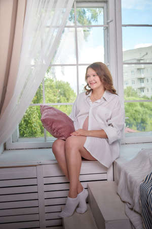 Cute pregnant woman in the living room. Beautiful pregnant future mother at home Standard-Bild