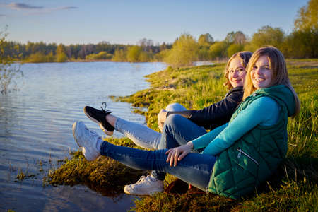 Two girls friends, sisters, cousins socializing and having fun on the shore or beach of a lake or river