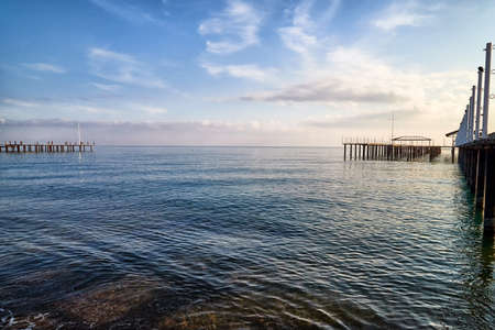 View from sand beach to water of sea, waves and pier in a nice day or evening with blues sky, bright sun and white clouds. The concept of a holiday on the sea or ocean in the South Stock Photo