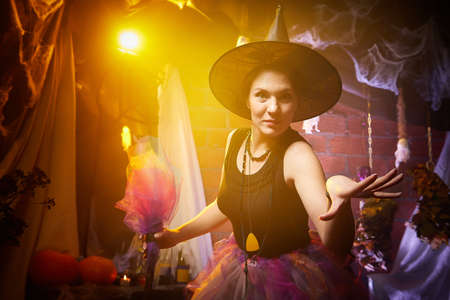 Young brunette witch with clouds of smoke behind her in Halloween location in studio. Witchcraft and wizardry in carnival Banque d'images