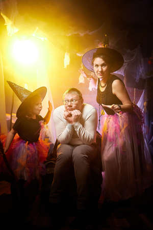 Beautiful brunette mother, cute little daughter looking as witches in special dresses and hats and father in casual dress in room decorated for Halloween. Halloween style family photo shoot.