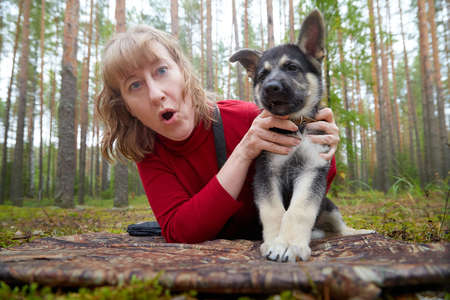 A girl in a red sweater playing with a small German shepherd puppy in the forest
