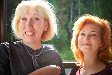 Portrait of two attractive middle-aged women. Blonde and red-haired woman posing together. Two interesting female friends