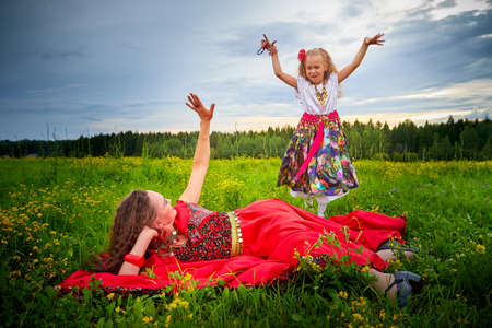 Mother and daughter in colorful Gypsy dresses resting and having fun in meadow with green grass. Little girl who is dancer or model dancing for adult woman looking as gypsy at summer evening on nature 版權商用圖片