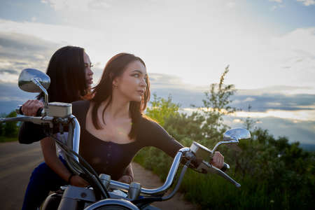 Two attractive female brunette motorcyclists with motorcycle in a summer evening and sky with clouds background. dventure and travel concept 版權商用圖片