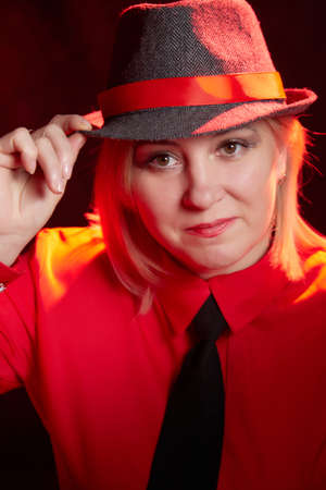 Portrait of fat plump chubby middle-aged woman with hat. Model posing in male style in the Studio.