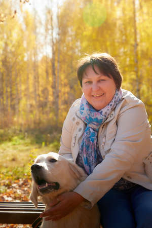 A plump woman with a white Labrador dog walking in a Park or forest on a Sunny autumn day