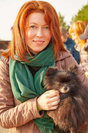 Cute girl with red long hair with dog in the autumn sunny day. Friendship woman and dog. 版權商用圖片