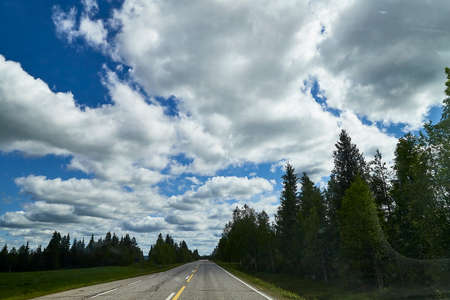 View from relief car windscreen on the blue sky with white clouds, gray asphalt road and landscape with forest and green treeses. Landscape through window. Trip for isolation in a coronavirus