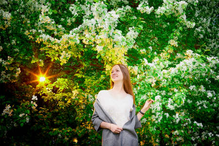 Outdoor portrait of a beautiful young girl near blossom apple trees with white flowers
