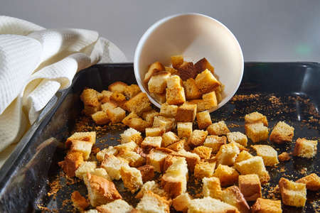 Square toasted pieces of homemade delicious rusk, hardtack, Dryasdust, zwieback on a white plate and baking sheet 版權商用圖片