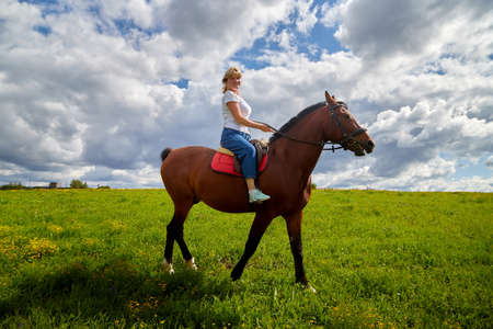 Girl riding on horse on a green field and a blue sky with white clouds on the background