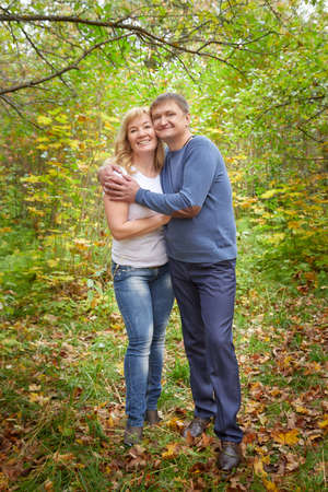 Middle-aged couple walking in the park on an autumn day