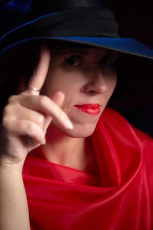 Portrait of ugle middle-aged woman with hat and red dress. Ugly model looking as lady posing in studio 版權商用圖片