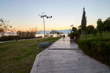 Antalya, Turkey - December 18, 2019: Embankment with people in evening in Antalya in Turkey