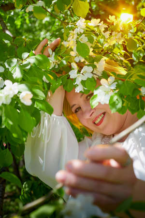 Outdoor portrait of a beautiful blonde middle-aged woman near blossom apple trees with white flowers. 版權商用圖片