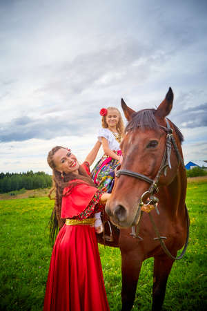 A woman and a girl in bright Gypsy dresses with a horse in a field with green grass. Mother and daughter pose in nature with an animal from a farm and the sky with clouds in the background