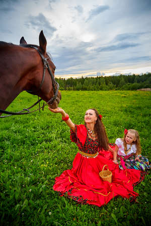 A woman in a bright Gypsy dress and image with a horse in a field with green grass. A model or actress posing in nature with an animal from a farm and the sky with clouds in the background