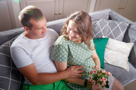 Cute couple including a pregnant woman and a caring man in the living room together 版權商用圖片