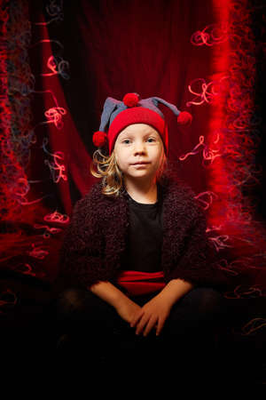 Little pretty girl looking like a dwarf or elf posing on a black and red background. 版權商用圖片