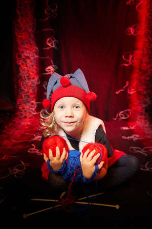 A pretty little girl who looks like a dwarf or elf is knitting with multicolored threads from large clubs on a black and red background. 版權商用圖片