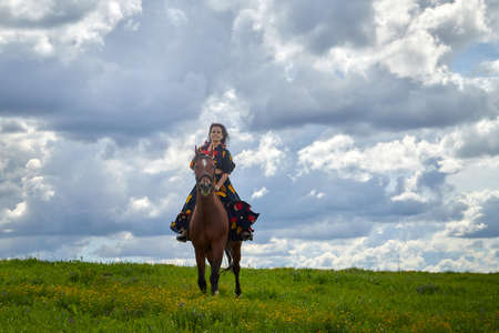 Beautiful gypsy girl rides a horse in field with green glass in summer day and blue sky and white clouds background. Model in ethnic dress posing with farm animal