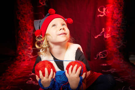 A pretty little girl who looks like a dwarf or elf is knitting with multicolored threads from large clubs on a black and red background