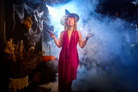 Blonde witch in red dress and black hat in Halloween decoration indoors with cell phone and smoke near her. Woman taking selfie during holiday carnival