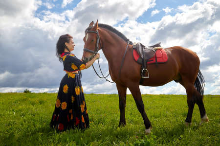 Beautiful gypsy girl with a horse in a field with green glass in summer day and blue sky and white clouds background. Model in ethnic dress posing with farm animal