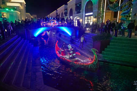 Belek, Turkey - December 18, 2019: A beautiful boat with fairy tale characters or theater actors floating on the water in the dark with colored lights.