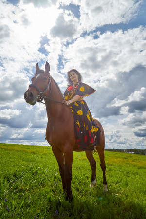 Beautiful gypsy girl on a horse in a field with green glass in summer day and blue sky and white clouds background. Model in ethnic dress posing with farm animal