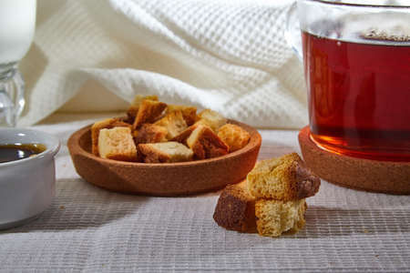 Square toasted pieces of homemade delicious rusk, hardtack, Dryasdust, zwieback on a plate and black tee in a cap on a white tablecloth Standard-Bild