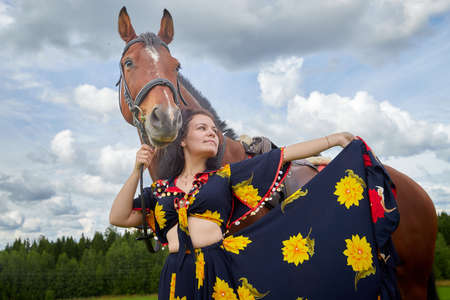 Portrait of beautiful gypsy girl with a horse on a field with green glass in summer day and blue sky and white clouds background. Model in ethnic dress posing with big animal