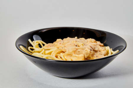 Long spaghetti in a black plate on white background 写真素材