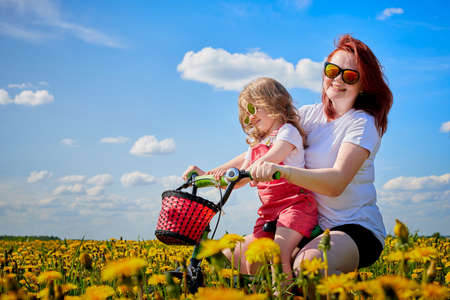 Mother and daughter wtht bicycle in a field with yellow dandelions. Family walks in the spring in nature