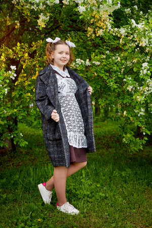 Portrait of a young girl in an old school uniform of the USSR with a black dress and a white apron. Teenager in the Park among the greenery after graduating from school in Russia.
