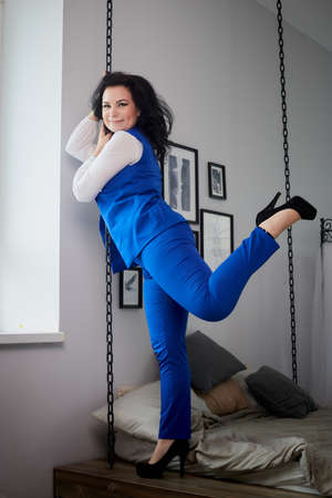 Kirov, Russia - May 31, 2020: Beautiful sexy brown curly long hair woman posing in nice room. Studio shooting in interior. Model in bed room. Happy glamorous woman in formal blue suit