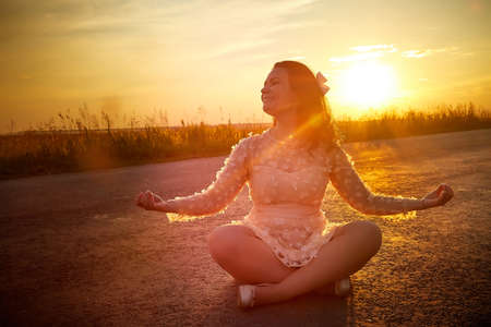 Beautiful sexy girl in pink dress sitting in the Lotus position like a yogi on the asphalt highway during sunset and field with grass on side of the road