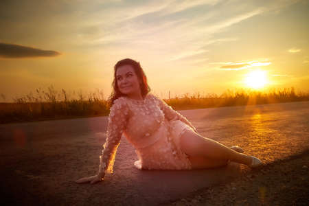 Beautiful sexy girl in pink dress sitting on the asphalt highway during sunset and field with grass on side of the road