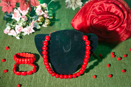 Red beads lying on an unusual surface and red bracelet 写真素材