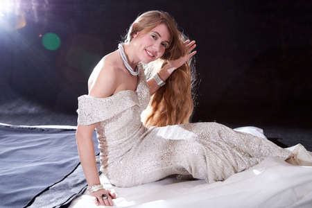Young attractive girl with long blonde hair and beautiful dress in studio on dark background